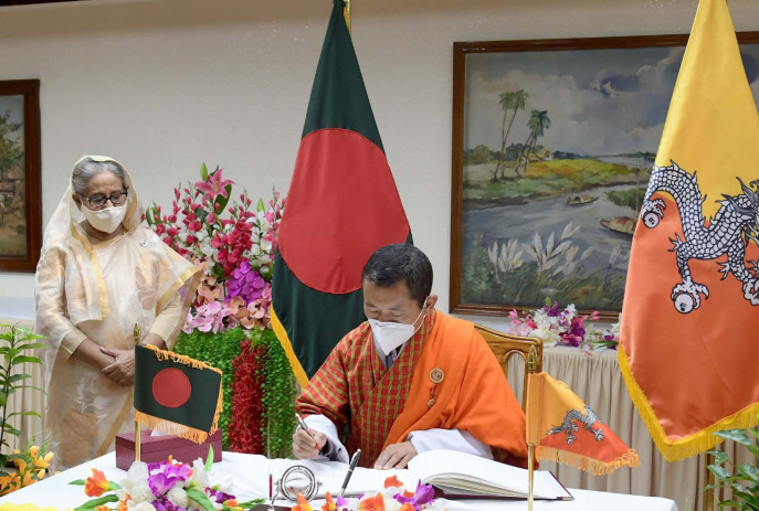 Prime Minister of Bhutan Dr Lotay Tshering signs Visitor's Book at Prime Minister's Office in Dhaka while Bangladesh's Premier looks on. Photo: PID